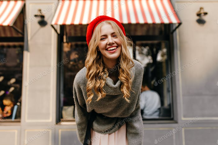 Portrait of curly hairstyle blonde attractive girl. Young woman in red French beret looking into th