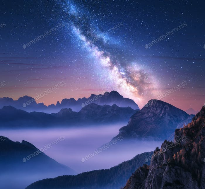 Milky Way over mountains in fog at night in summer