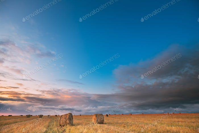 Dramatic Sky Before Rain With Rain Clouds On Horizon Above Rural Landscape Field Meadow With Hay