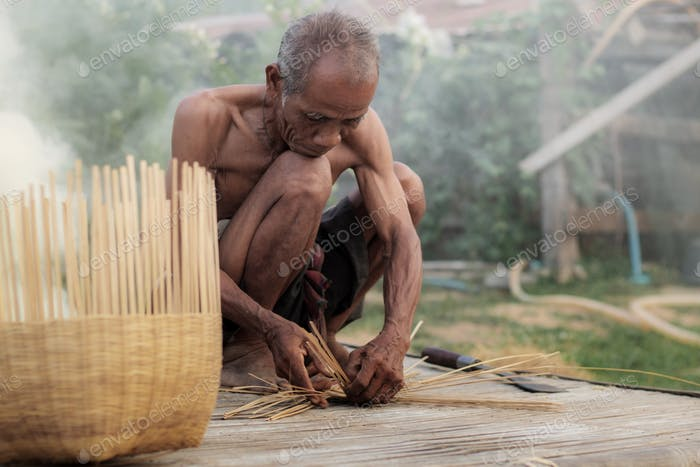 Old man are weaving basket