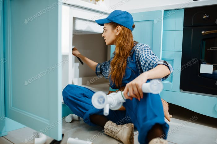 Female plumber fixing problem with drain pipe