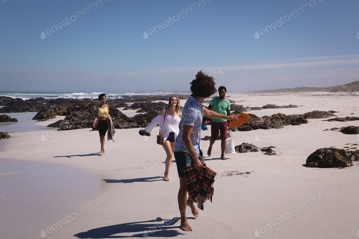 Front view of a group of multi ethnic friends walking on the beach and having fun in the sunshine