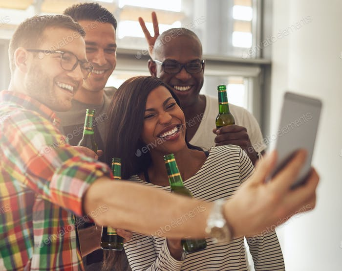 Cheerful team taking the�selfie with beer