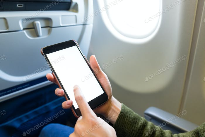 Holding digital mobile phone at airplane