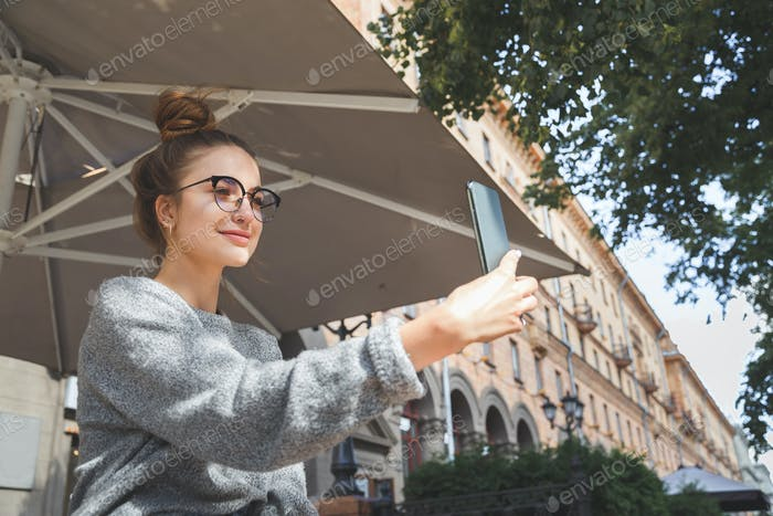 Young caucasian woman making selfie or video chattintg online with phone standing on the street