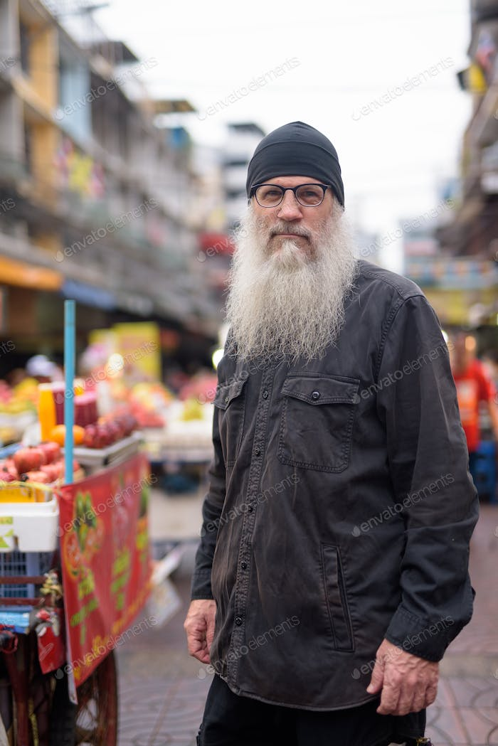Mature bearded tourist man with eyeglasses in Chinatown