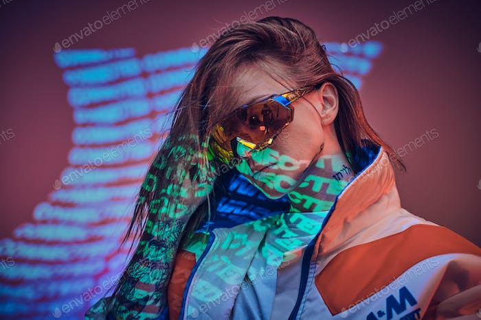 Close up portrait of a young tattooed racer woman posing in a vivid neon studio over text projection