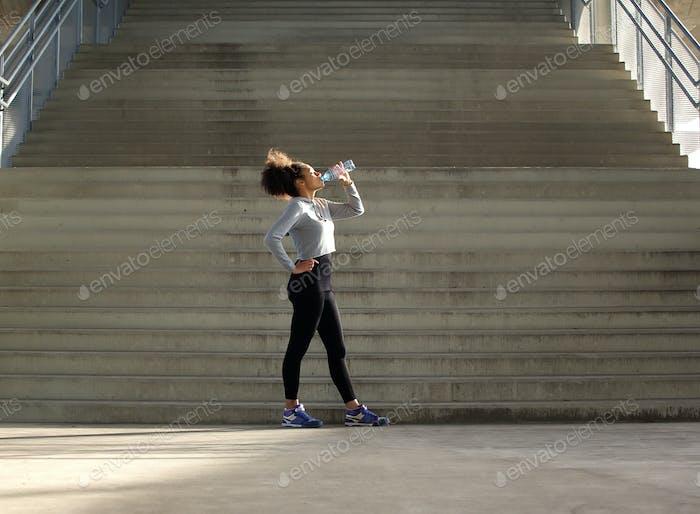 Sport woman drinking water from bottle