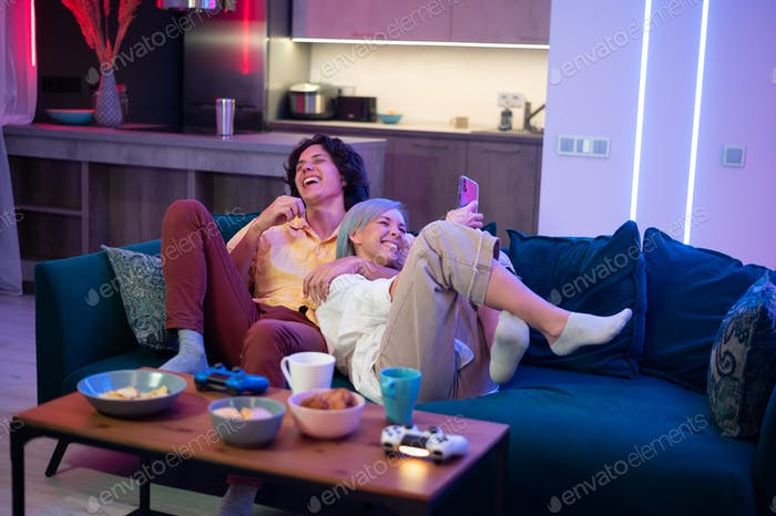 Happy boyfriend and girlfriend laughing after playing video games at home, joysticks and snacks on a
