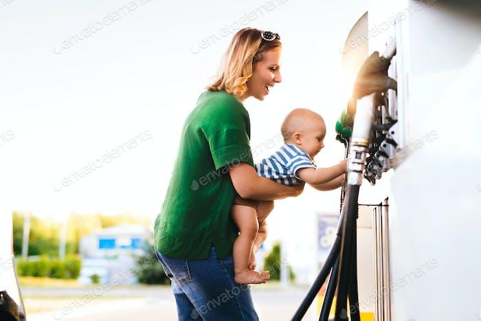 Junge Mutter mit Baby Junge an der Tankstelle.