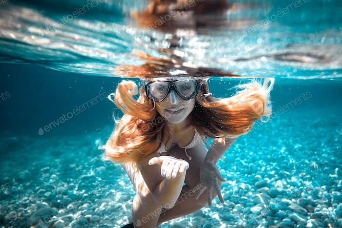 Hermosa mujer con el pelo largo retrato bajo el agua en el mar tropical