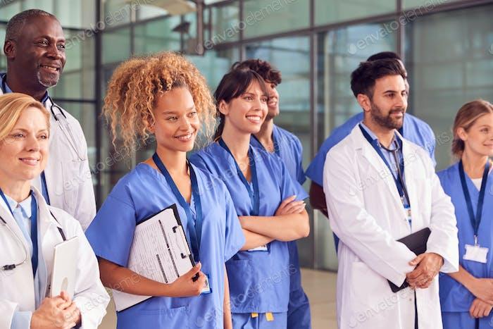 Smiling Medical Team Standing In Modern Hospital Building