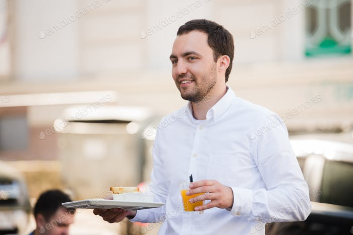 Portrait of happy waiter holding breakfast meal and orange juice at outdoor cafe