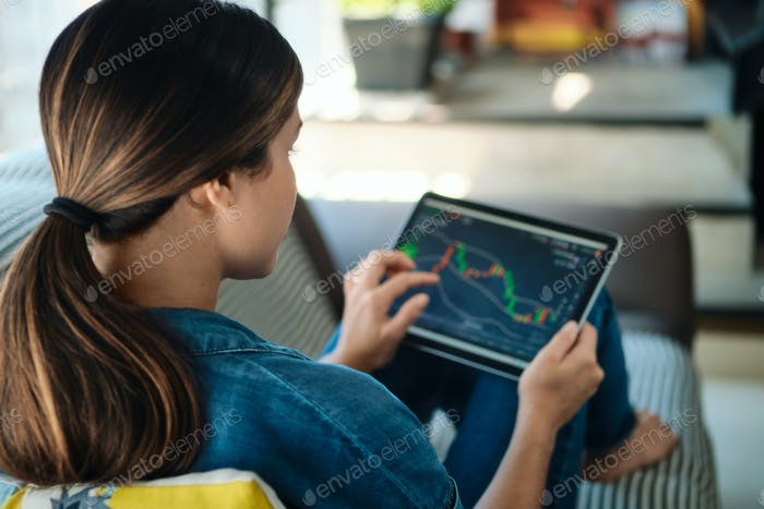 Woman Trading Online With Tablet On Sofa