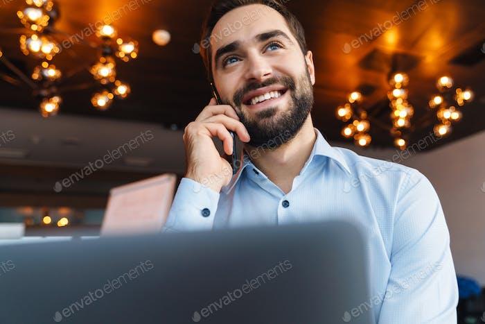 Porträt des Geschäftsmanns im Gespräch auf dem Handy während der Arbeit im Büro