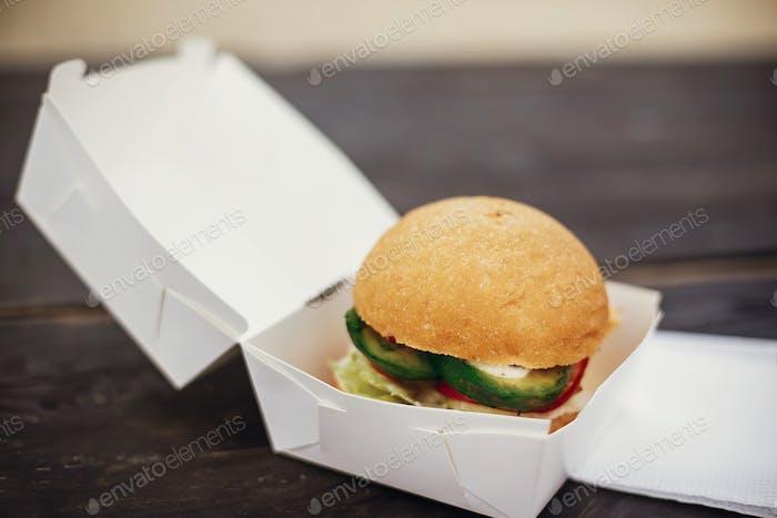 Delicious vegan burger with avocado and beets in carton tray