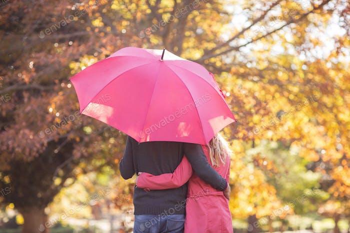 Couple embracing while holding umbrella