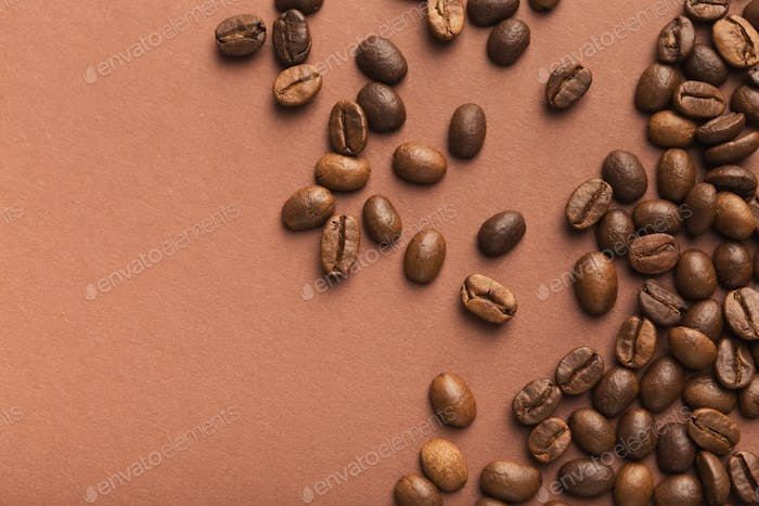 Heap of brown coffee beans on pink background