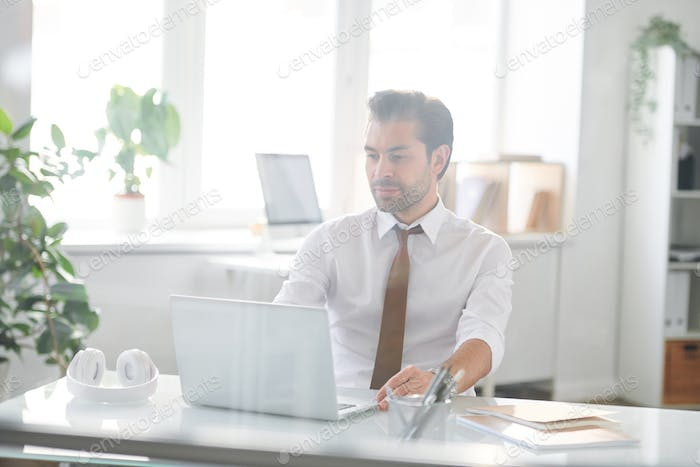 Young confident businessman sitting by desk in office in front of laptop