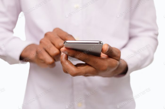 Black man using smartphone, browsing social media over white background