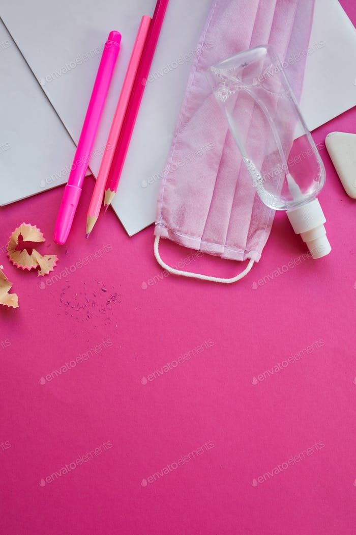 School supplies, protective mask and antiseptic on a pink background