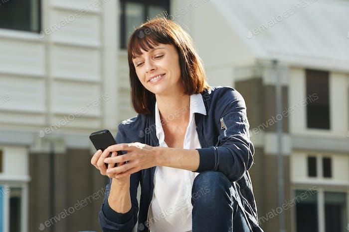 Glückliche Frau mit Handy sitzen außerhalb