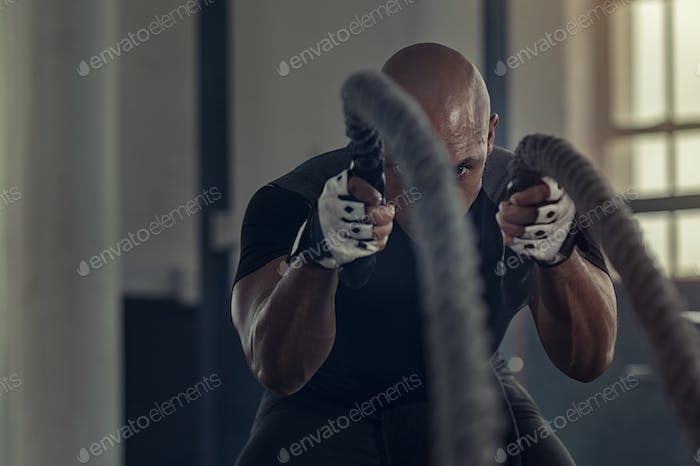 Black man doing intensive battle rope workout