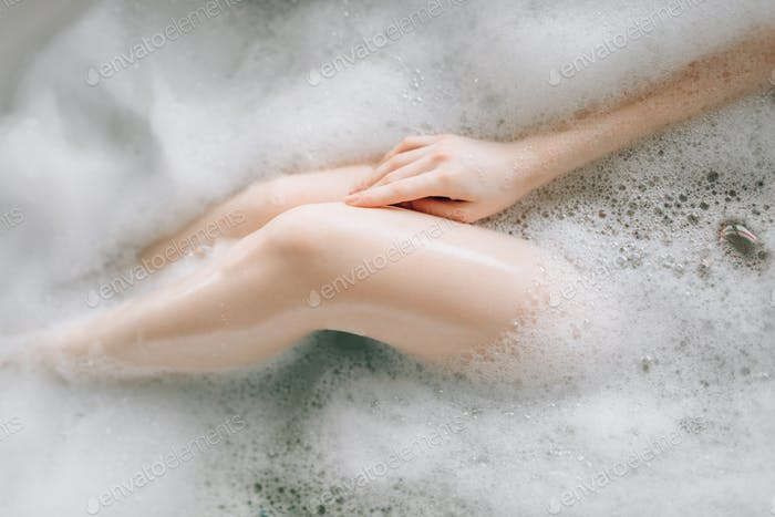 Nude legs of female person lying in bath with foam