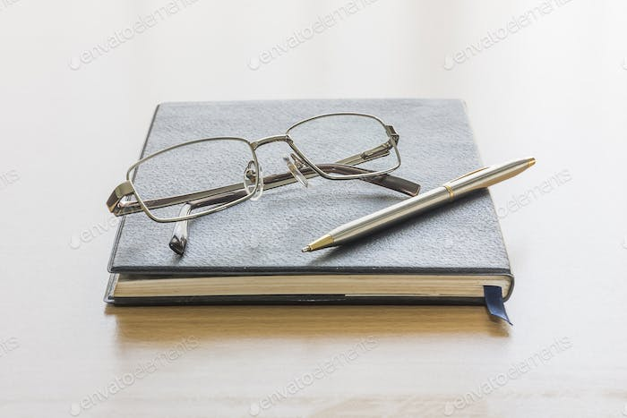 Black book with glasses and pen