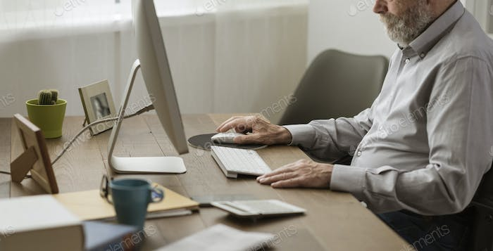 Senior man using his computer at home