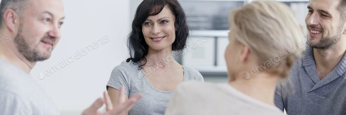 Smiling people talking with psychologist