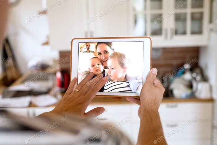 Father at home with tablet, video chatting with his family.