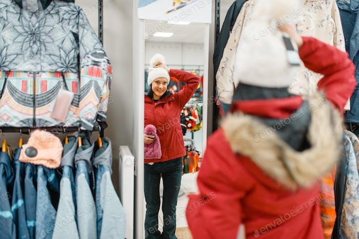 Woman at the showcase choosing ski suit, shopping