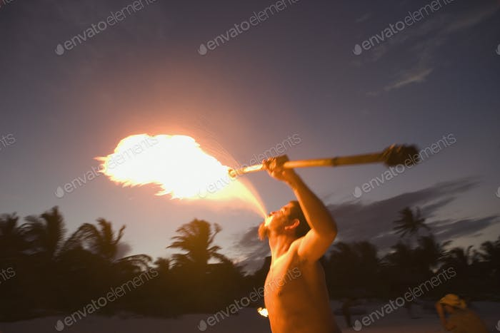 Man performing and breathing fire