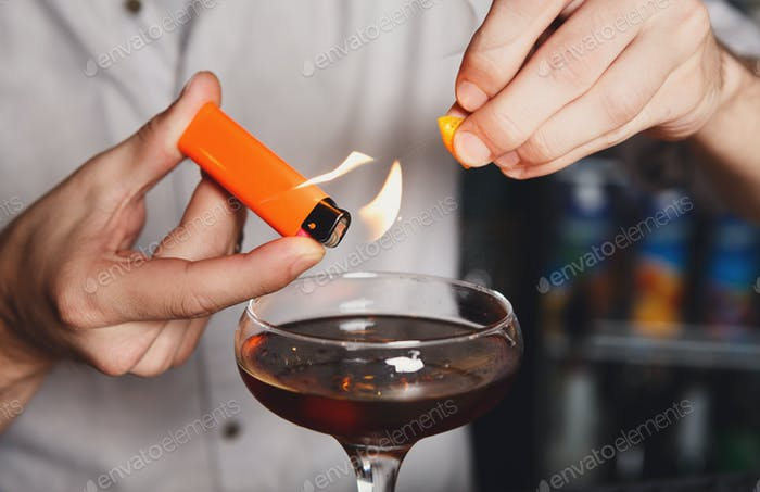Manos del barman haciendo un cóctel en llamas