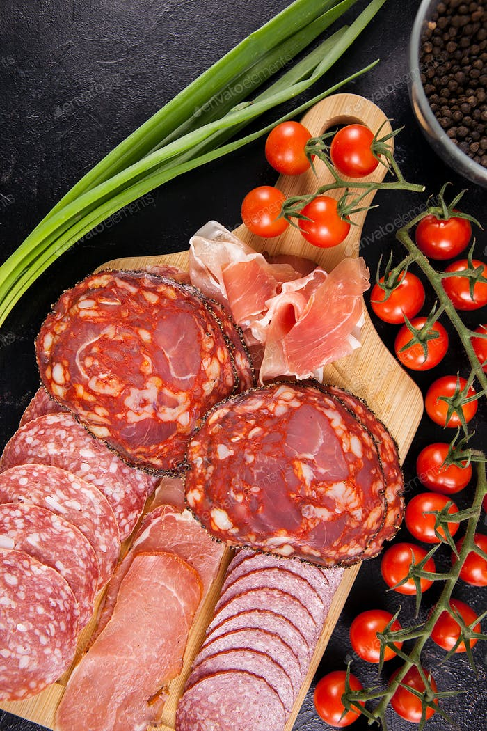 Top view of meat appetizers on wooden board