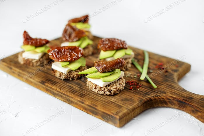 Sandwiches with cheese, avocado and dried tomatoes. Concept for food, healthy food and vegetarians.