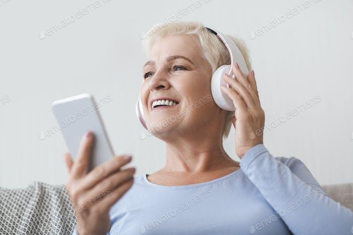 Senior woman enjoying music and watching videos on smartphone
