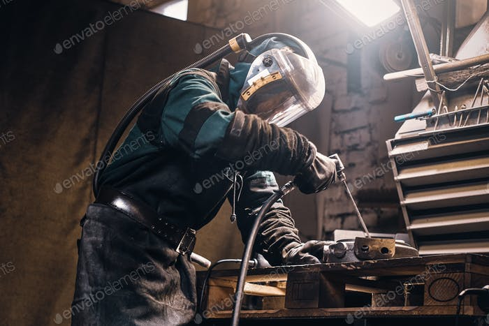 Busy man is working on metal factory
