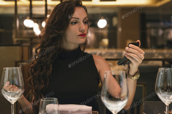 Attraktive weibliche Verwendung Spiegel Make-up im Restaurant