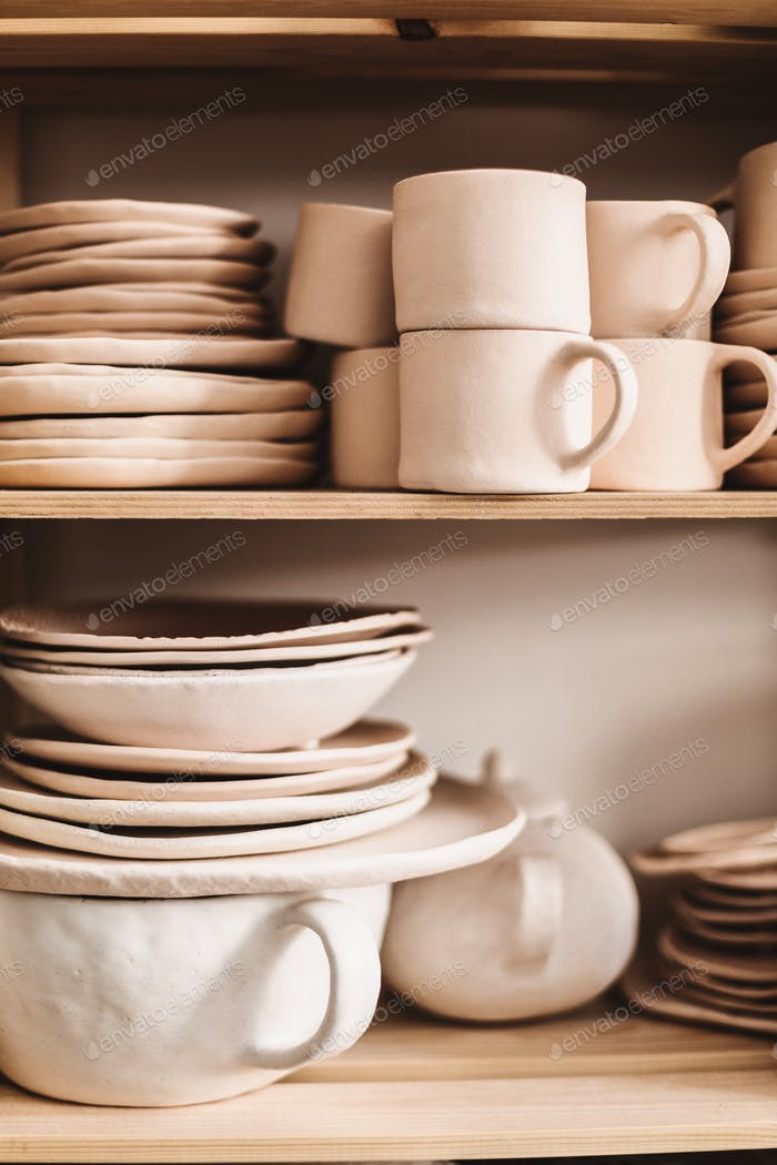Close up handmade classic clay dishes on wooden shelves at pottery studio isolated