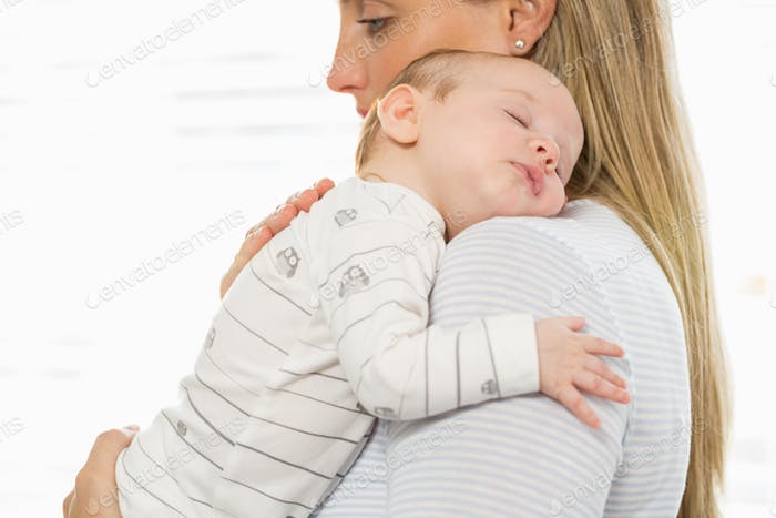 Mother holding and embracing her baby boy