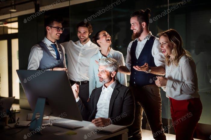 Eine Gruppe von Geschäftsleuten mit Computer in einem Büro, die Aufregung zum Ausdruck bringen
