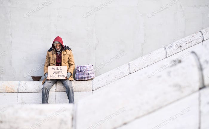 Homeless beggar man sitting in city holding cardboard sign. Copy space.