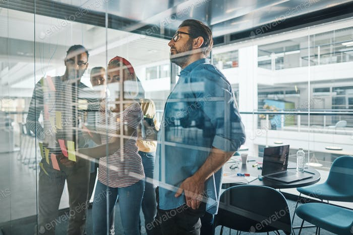 Diverse businesspeople brainstorming on a glass wall with sticky notes