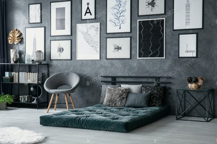 Grey armchair next to green mattress in bedroom interior with ga