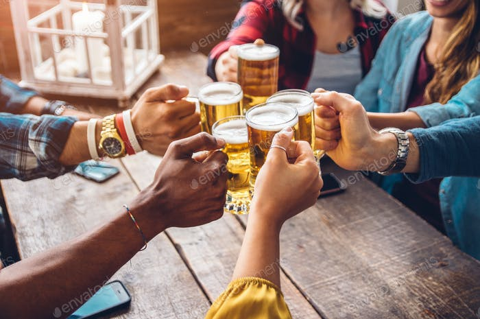 Happy diverse young people celebrating together toasting beers