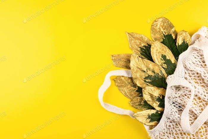 Bolsa reutilizable con hojas verdes y doradas sobre fondo amarillo otoño otoño. Vista superior de