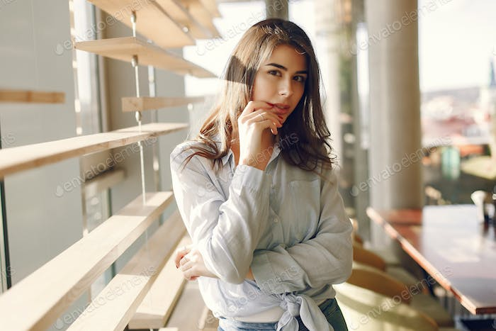 Smiling girl in a blue shirt standing near window and posing