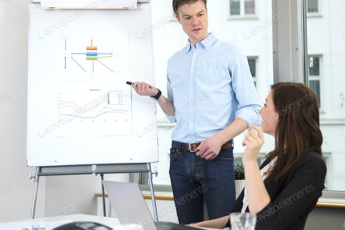 Businessman Giving Presentation To Colleague In Office